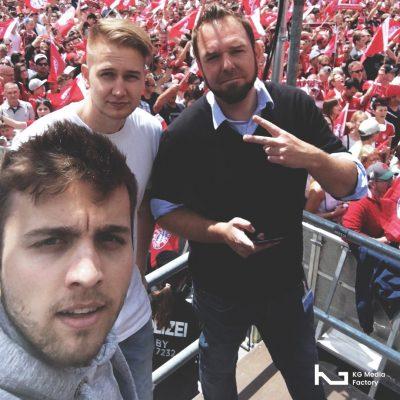 Drei Mitarbeiter posen vor der Kamera. Im Hintergrund sind viele Bayern Fans